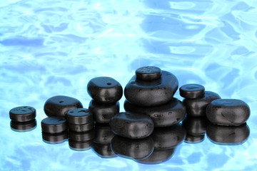 Spa stones with droplets on blue background