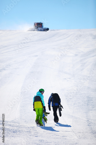 Two snowboarders walking up slope