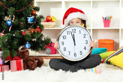Little girl holding clock near christmas tree