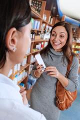 Kundin in der Drogerie hält Kosmetikprodukt in der Hand