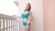 Pretty sexy bikini blond woman in motion on balcony