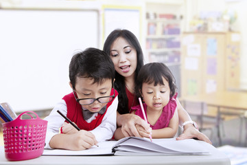 Teacher and children study in classroom
