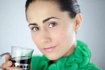 Piękna kobieta w zieleni pijąca herbatę
