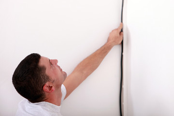 Electrician wiring a wall