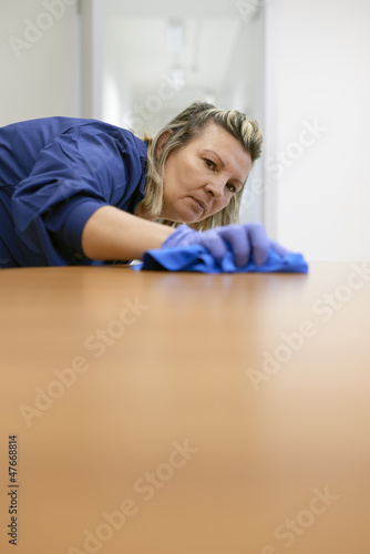 Professional female cleaner wiping table in office