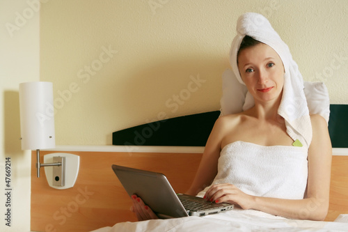young business woman working at the note book in the bed