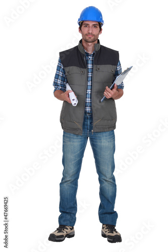 Tradesman holding rolled-up blueprints and a clipboard