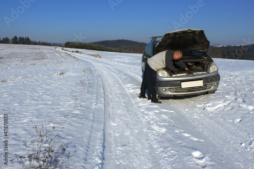 man repairing the car on a deserted road, winter weather