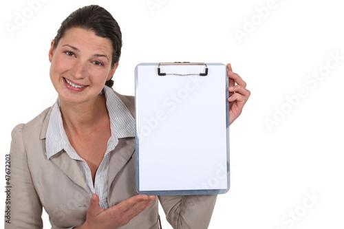 Brunette presenting blank clip-board