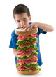 Cute child making big sandwich isolated on white