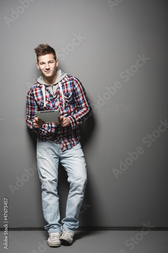 Smiling young urban man with a tablet