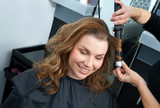 woman curling hair in hairsalon poster