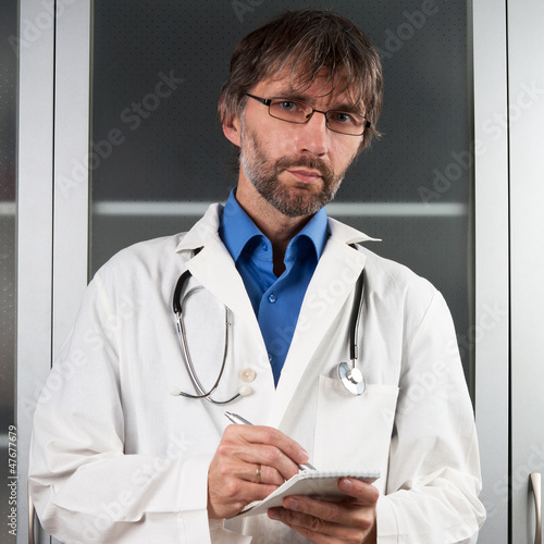 doctor writes in a notebook