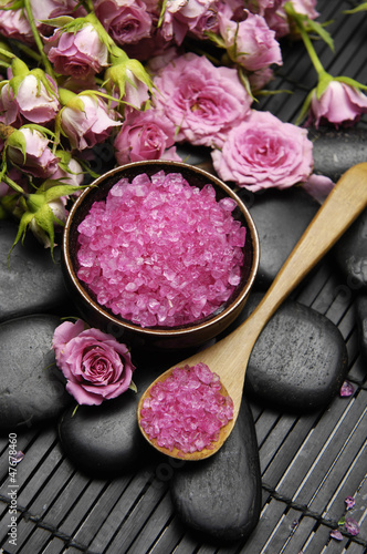 Beautiful pink orchid with salt in spoon and stones on mat