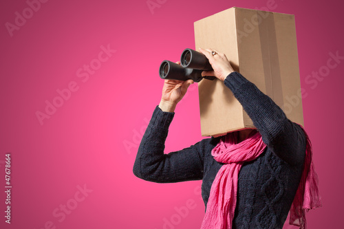 Girl with cardboard box head looking through binoculars