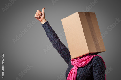 Girl with cardboardbox head showing her thumb up