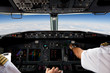 Leinwanddruck Bild - Pilots Working in an Aeroplane During a Commercial Flight