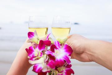 Мужская и женская руки держат бокалы с вином. Букет орхидей.