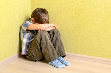 Little child boy wall corner punishment sitting
