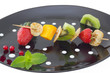 Mini blini (pancake) with cut fruits on skewers, on black plate.