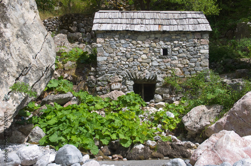 stone watermill with shingle roof along Shala river in Theth Valley, Albania
