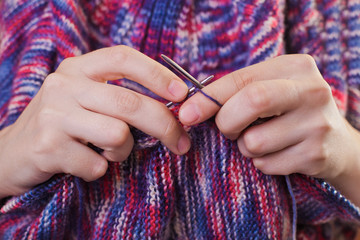 Hands with knitting needles closeup