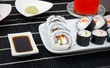Sushi set on white plate. Black bamboo mat background