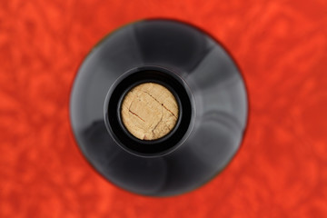 Wine bottle top view on red background
