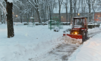 snowplow Tractor cleaning snow in the park