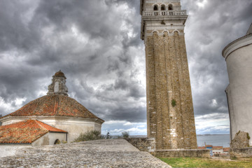 Saint George's Parish Church in Piran, under a threatening sky,
