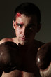 Man in boxing gloves with blood on a face