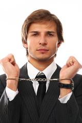 Handsome businessman hands in handcuffs
