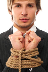 Handsome businessman hands tied with rope