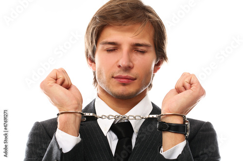 Handsome businessman hands in handcuffs