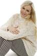 Hübsche blonde Frau sitzt am Boden und lächelt
