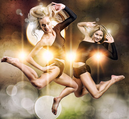 Two beautiful athletic girl jumping over abstract background