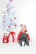 Kleines Mädchen sitzt unterm Weihnachtsbaum