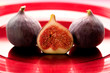 Several figs on a red palte