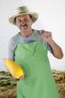 Bauer mit einem gelben organischen Kürbis in der Hand