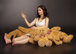 brunette woman posing in luxurious dress playing with teddy bear