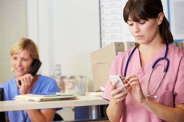 Nurse Using Mobile Phone At Nurses Station
