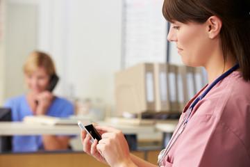 Nurse Using Mobile Phone At Nurses Station