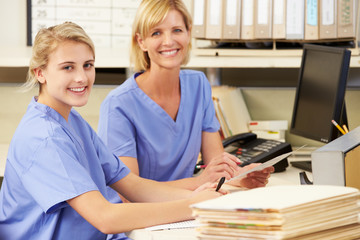 Two Nurses Working At Nurses Station
