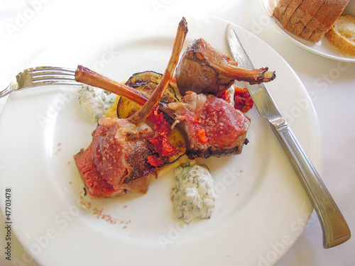 Lamb chops served on a bed of vegetables on a white plate
