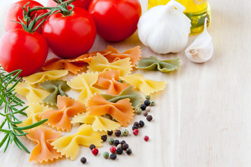 Ingredients for Italian cuisine: farfalle pasta, tomatoes, olive