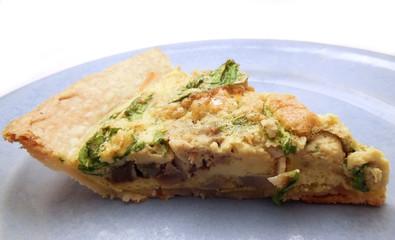 Slice of quiche with artichoke and arugula