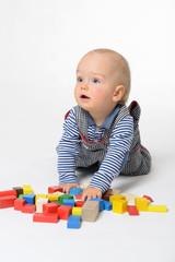 Junge spielt mit Holzbausteinen