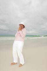 Mature woman active retirement storm beach isolated