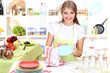 A young girl dries dishes in kitchen