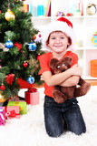 Little boy in Santa hat sits near Christmas tree with gift in